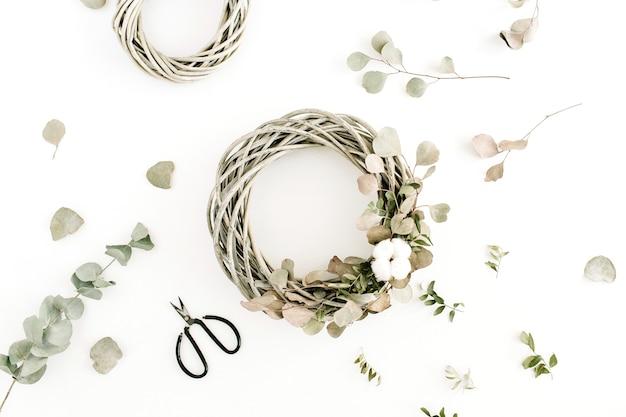 Cadre de couronne avec des boules de coton et une branche d'eucalyptus sur fond blanc. mise à plat, vue de dessus