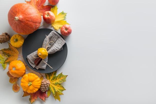 Cadre de couverts, verres à vin, assiette, citrouilles, feuilles, pommes sur gris. vue de dessus.