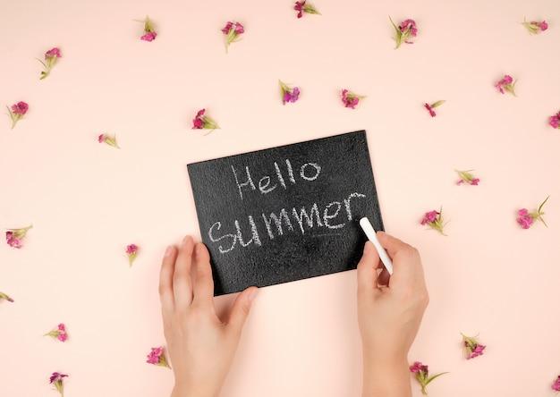 Cadre de craie noire avec une inscription bonjour l'été et deux mains féminines