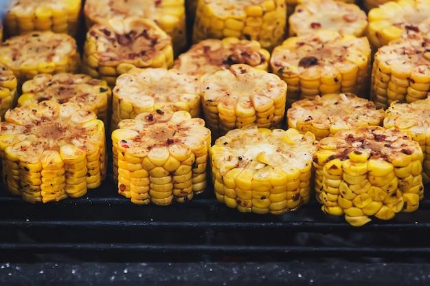 Cadre de cuisson. nourriture délicieuse sur le gril. le processus de cuisson des légumes sur le gril. frit de différents côtés des morceaux de maïs jaune.