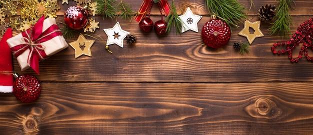 Cadre avec décor de noël sur un fond en bois. nouvel an, ambiance de vacances, branches d'épinette verte, décorations: étoiles, coffret cadeau, perles, boule, cloches, cônes. espace pour le texte, pose à plat
