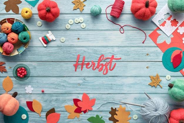Cadre décoratif composé de faisceaux de laine, de boules de fil, de citrouilles décoratives en feutre et de feuilles d'automne colorées. texte papier herbst