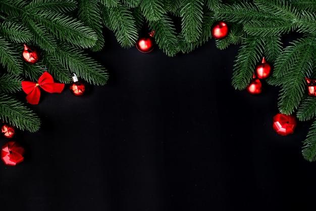 Cadre de décoration de noël avec des branches de sapin et des boules rouges sur noir
