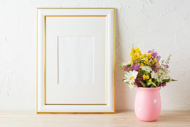 Cadre décoré d'or avec des fleurs sauvages dans un vase rose