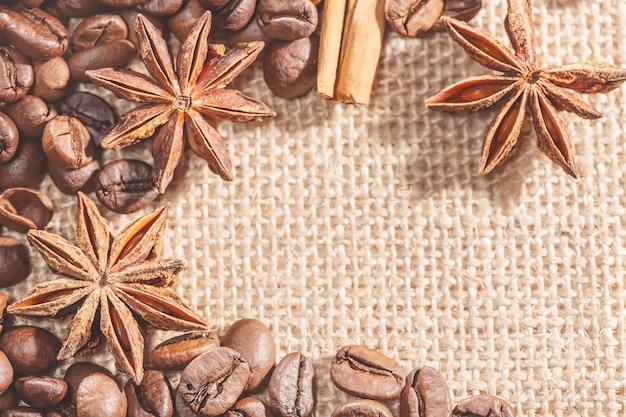 Cadre design avec des grains de café, des stocks de cannelle sur un sac avec des épices anis. image gros plan