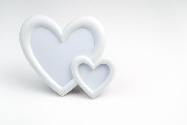 Cadre de deux coeurs blancs sur fond clair. vue latérale avec espace pour la copie.