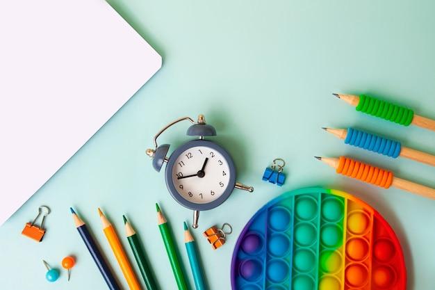 Cadre de différentes fournitures scolaires sur fond bleu. concept de retour à l'école, vue de dessus.