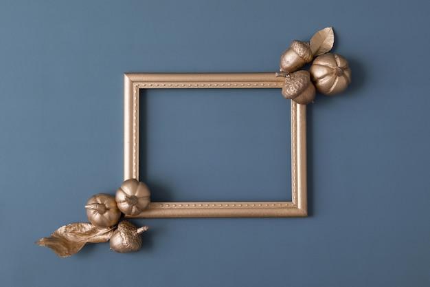 Cadre doré avec des citrouilles laisse des glands sur un fond gris avec un espace de copie concept d'automne créatif