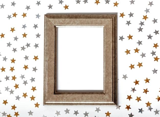 Cadre doré. des étoiles de confettis dorées et argentées brillent sur un fond blanc isolé. espace de copie