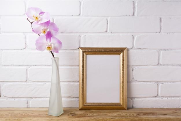 Cadre doré avec orchidée rose tendre