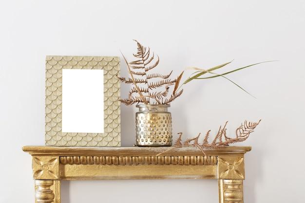 Cadre doré et plantes séchées sur mur blanc