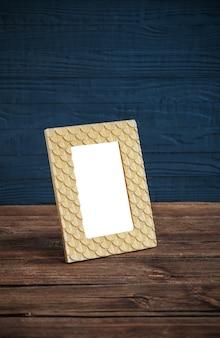Cadre doré sur table en bois sur fond de bois bleu