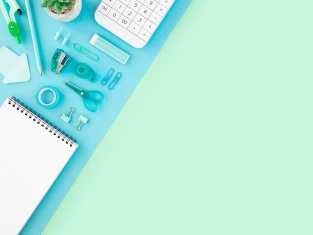 Cadre d'école minimal à plat. fournitures de ton bleu étudiant sur le bureau. copiez l'espace.