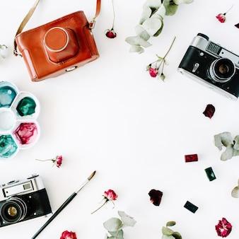 Cadre d'espace de travail d'artiste avec appareil photo rétro vintage et arrangement d'aquarelle, de roses rouges et d'eucalyptus