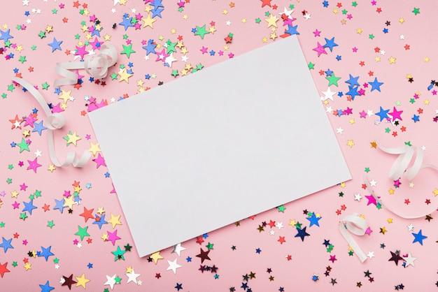 Cadre avec des étoiles de confettis colorés sur fond rose