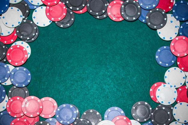 Cadre fabriqué avec des jetons de casino sur une table de poker verte