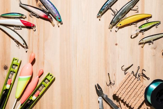 Cadre fabriqué avec un leurre de pêche; flotteur de pêche; pince; crochets sur fond en bois