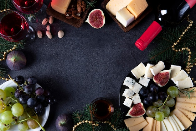 Cadre fabriqué à partir de variétés de fromage, de fruits et de noix sur fond sombre. collation du réveillon du nouvel an