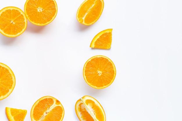 Cadre fait d'agrumes orange frais avec des feuilles isolées sur une surface blanche. juteux et sucré