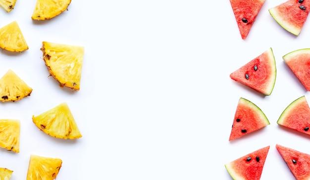 Cadre fait d'ananas avec des tranches de pastèque sur fond blanc.