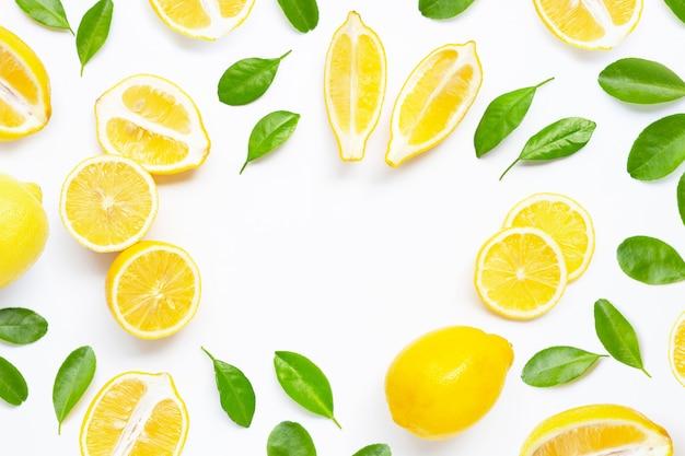 Cadre fait de citron frais avec des feuilles vertes sur blanc.