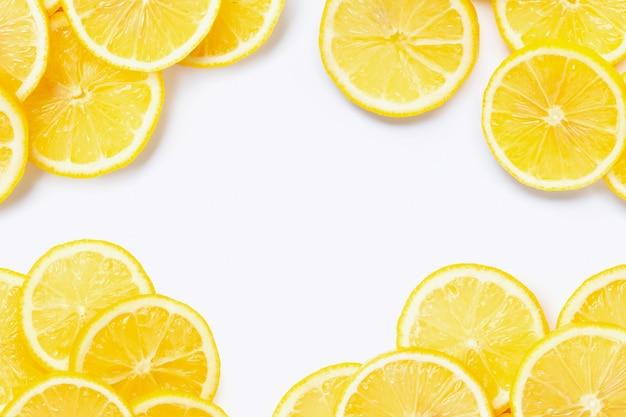 Cadre fait de citron frais avec des tranches sur le blanc.