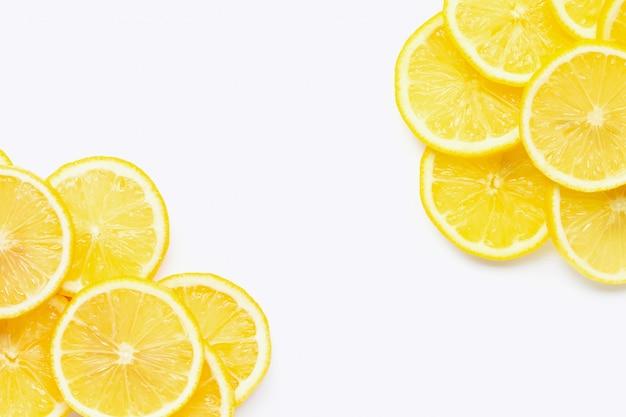 Cadre fait de citron frais avec des tranches sur fond blanc.