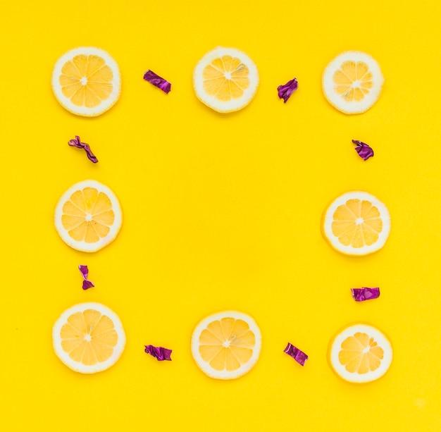 Cadre fait avec des citrons en tranches et du chou violet haché sur fond jaune