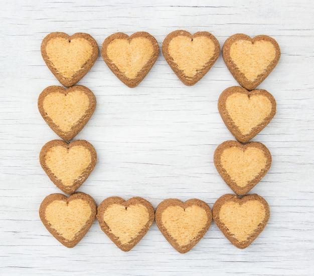 Cadre fait de cookies avec des coeurs sur fond blanc