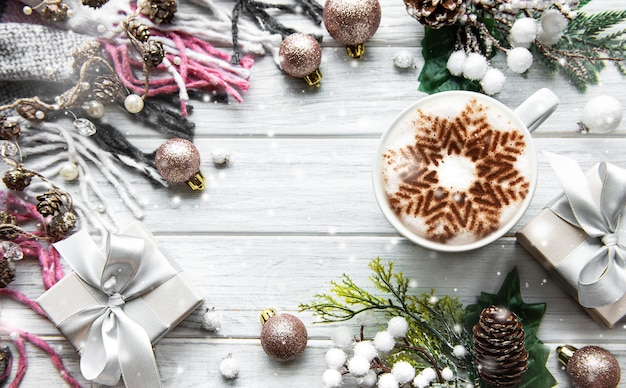 Cadre fait de décorations et de café avec flocon de neige sur une surface en bois blanche