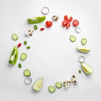 Cadre fait de différents légumes frais sur blanc, vue du dessus