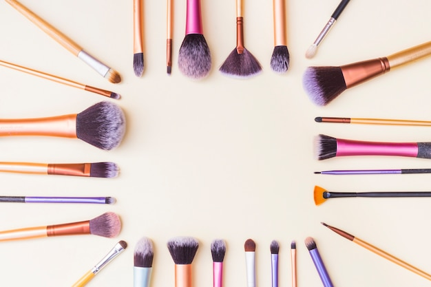 Cadre fait avec un ensemble de pinceaux de maquillage sur fond beige
