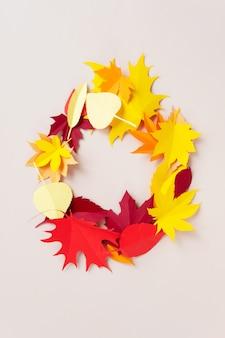 Un cadre fait de feuilles d'automne sur fond beige. les feuilles sont découpées dans du papier