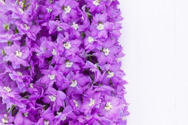 Cadre fait de fleurs de delphinium lilas sur fond de planche blanche. vue de dessus. espace de copie.