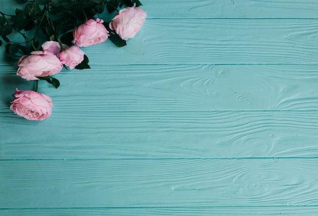 Cadre fait de fleurs roses roses sur un fond en bois bleu.