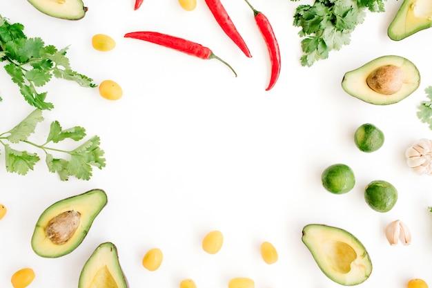Cadre fait d'ingrédients alimentaires crus de guacamole: avocat, piment, coriandre, tomate cerise, citron vert, ail