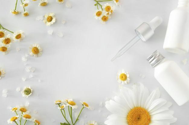Cadre fait de produits cosmétiques avec des fleurs de camomille sur fond blanc