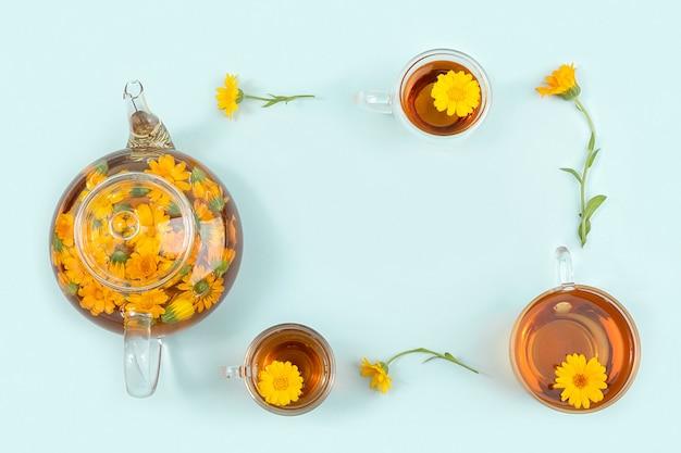 Cadre fait de tasses de tisane, de théière transparente et de fleurs de calendula sur fond bleu. concept de boisson apaisante. espace de copie vue de dessus mise à plat.