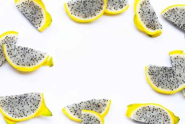 Cadre fait de tranches de pitahaya jaune ou de fruits du dragon sur fond blanc.