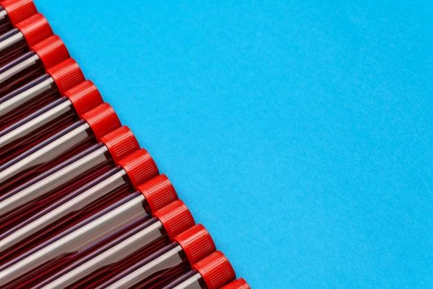 Cadre fait de tubes à essai de médecine avec des échantillons de sang