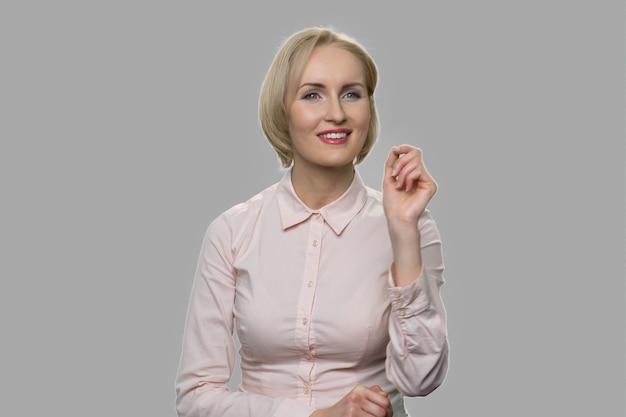 Cadre féminin travaillant sur écran virtuel. jolie jeune femme d'affaires à l'aide d'une interface imaginaire sur fond gris.