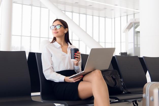 Cadre féminin avec valise en voyage d'affaires lié au travail en attente de son vol dans un aéroport