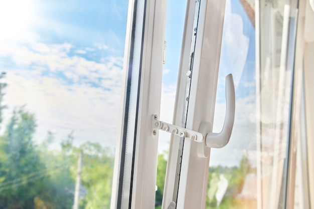Cadre de fenêtre en plastique ouvert. pose de fenêtre en plastique. ventilation de l'appartement par la fenêtre. matin ensoleillé à l'extérieur de la fenêtre en plastique blanc.