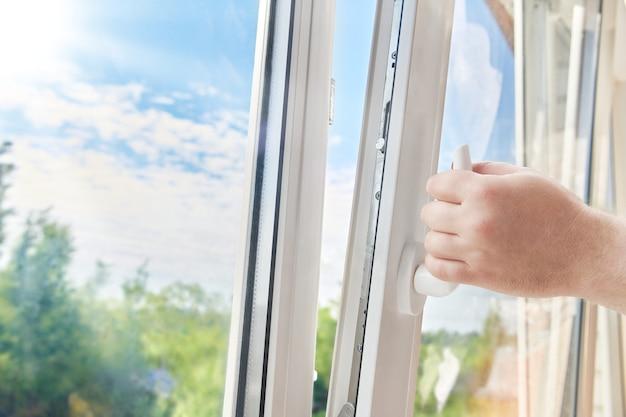 Cadre de fenêtre en plastique d'ouverture de main d'homme. ventilation de l'appartement par la fenêtre. matin ensoleillé à l'extérieur de la fenêtre en plastique blanc.