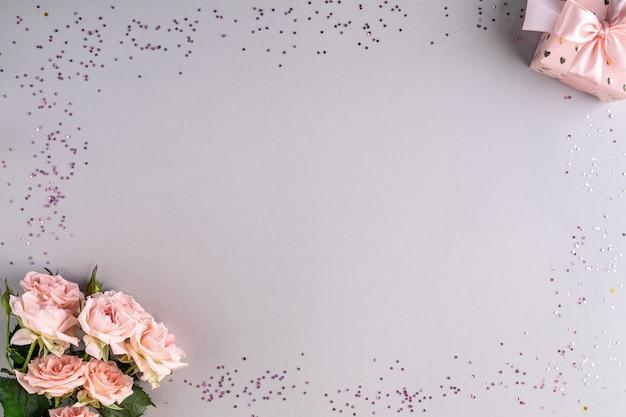 Cadre festif avec des roses roses et un cadeau sur une surface grise