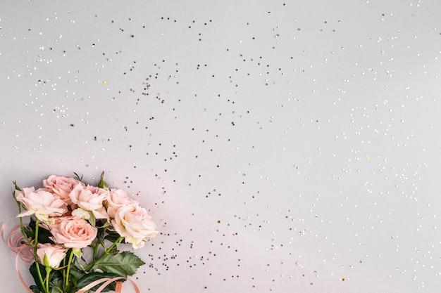 Cadre festif avec des roses roses sur fond gris