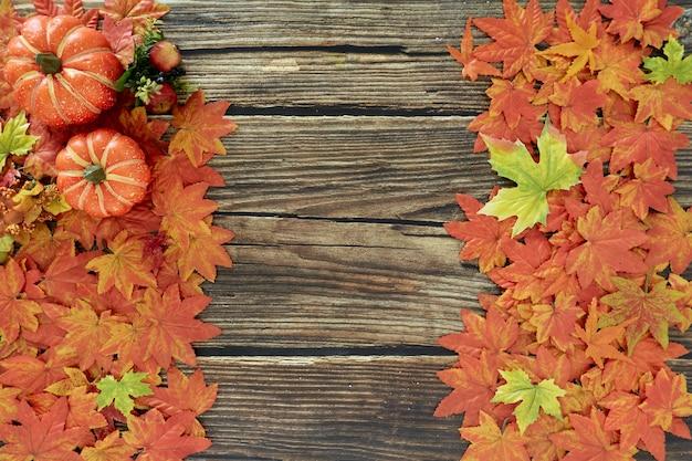 Cadre de feuilles d'automne et de citrouilles vieux fond en bois avec espace copie