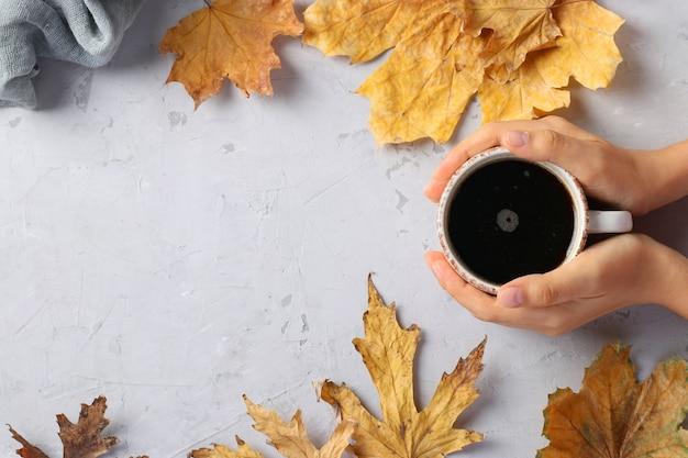 Cadre avec des feuilles d'automne et une tasse de café dans les mains des femmes sur fond gris, vue de dessus, mise à plat, espace de copie