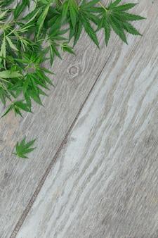 Cadre avec des feuilles de cannabis. fond avec de la marijuana sur fond de bois ancien