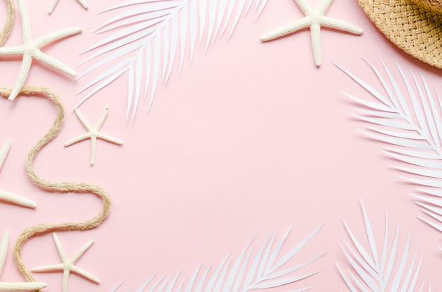 Cadre de feuilles de palmier, étoiles de mer et chapeau de paille